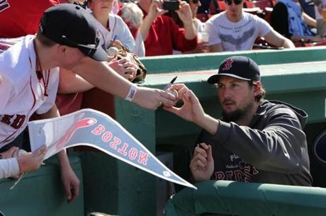 Joel Hanrahan, who is on the disabled list with a hamstring injury, signs autographs for fans before the game.